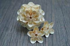 Yellow origami kusudama flower. On wooden background stock photo