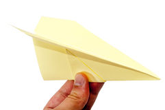 Yellow origami plane in the hand over white background.  Royalty Free Stock Photo