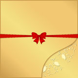 Yellow ornament in the lower right corner on a gold background with red ribbon and bow on tsentru. Stock Images