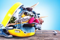 Yellow Trunk Different Things Accessories Travel. Yellow Overloaded Trunk Different Things Accessories Clothes Sunglasses Towels Passport Bikini Tickets Coat Royalty Free Stock Photo