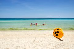 Yellow paddle boards and children boats on tropical beach. With white sand stock images