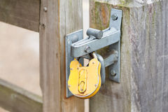 Yellow padlock on a closed gates Royalty Free Stock Photos