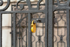 Yellow padlock on gate Royalty Free Stock Images