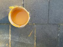 Yellow paint can. Yellow point can on concrete paving stones in sunshine stock photography