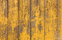 Yellow paint is peeling from a board wall Royalty Free Stock Photography