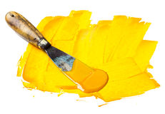 Yellow paint. Yellow printing press color with spatula isolated on white stock photography