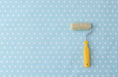 Yellow paint roller over blue polka dot wallpaper. In nursery room royalty free stock photography