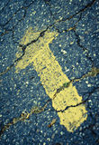 Yellow painted arrow on cracked pavement Royalty Free Stock Image