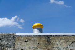 Yellow painted bollard on a quay Royalty Free Stock Photo
