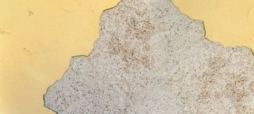 Yellow painted building and cracked hole and broken material facade. Structure Stock Photography