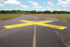 Yellow painted cross on asphalt with clouds in background Royalty Free Stock Photo