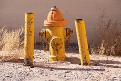Fire hydrant and protection poles in front of a block wall royalty free stock photos