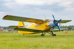 Yellow painted legendary soviet aircraft biplane Antonov AN-2 parked on a green grass of airfield against cloudy sky stock photos