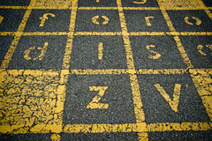 Yellow Painted Letters on Asphalt Royalty Free Stock Photos
