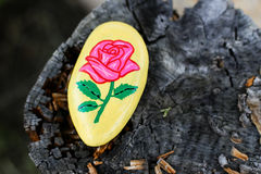 Yellow painted rock with pink rose Stock Photo