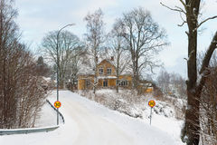 Yellow painted Swedish wooden house in a wintry landscape Royalty Free Stock Image