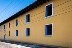 Yellow painted townhouse with blue windows. Typical painted colonial style townhouse in UNESCO World Heritage Site, Antigua, Guatemala Stock Photos