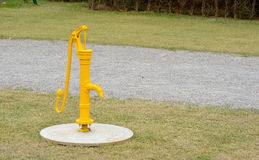 Yellow painted vinatge water pump. On the lawn Royalty Free Stock Image