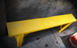 Yellow painted wooden bench. Bright yellow painted wooden bench in an apparently unfurnished room with bare stone walls royalty free stock photography