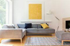 Yellow painting and lamp in modern living room interior with grey corner sofa. Real photo royalty free stock photography