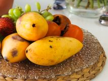 Papaya persimmon fruit and grapes lie on the tray Royalty Free Stock Photo