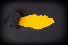 Yellow paper background appearing behind torn black paper Stock Photos