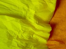 Yellow paper background silk surface empty blank sheets vivid colors. Orange Stock Images