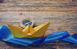 Yellow paper boat and old compass Royalty Free Stock Image