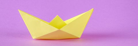 Yellow paper boat from origami with an autumn leaf on a purple background.  royalty free stock image