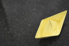 Yellow paper boat on wet asphalt, mood concept, copy space royalty free stock photo