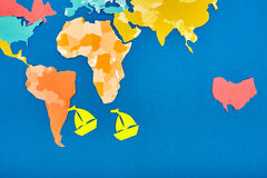 Yellow paper boats and international map while cut out of the colored paper on the blue background. Stock Images