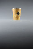 Yellow paper cup on grey Royalty Free Stock Image