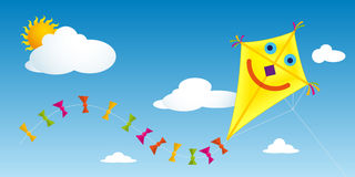Yellow paper kite with happy face and tail with colorful bows flying in a blue sky with clouds Stock Photo