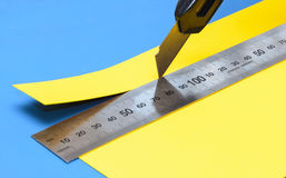 Yellow paper with a knife and a stainless steel ruler. Cuts off a piece of yellow paper with a knife and a  stainless steel ruler on blue cutting mat Royalty Free Stock Images