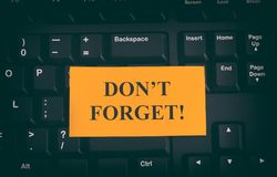 Yellow paper note on black keyboard with writing Don`t Forget!. Close up Stock Photography