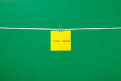 Yellow paper note on clothesline with text Call Now! Royalty Free Stock Images