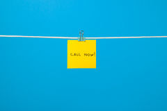 Yellow paper note on clothesline with text Call Now! Stock Image