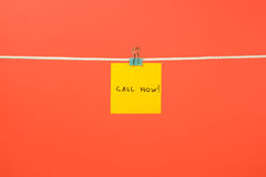 Yellow paper note on clothesline with text Call Now! Stock Photo