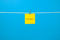 Yellow paper note on clothesline with text Friday Stock Images