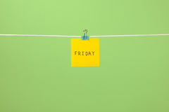 Yellow paper note on clothesline with text Friday Stock Photography