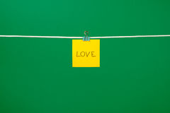 Yellow paper note on clothesline with text Love Royalty Free Stock Images