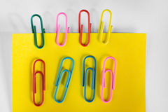 Yellow paper note with colorful paper clips. Royalty Free Stock Photos