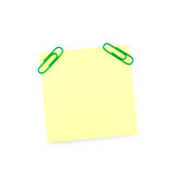 Yellow paper note with green clips Stock Images
