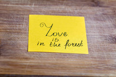Yellow paper note with love is in the forest  sign  on a wooden background Royalty Free Stock Photography