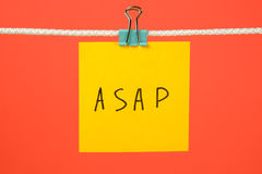 Yellow paper note on the string with text ASAP Stock Image