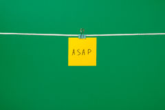 Yellow paper note on the string with text ASAP Stock Photography