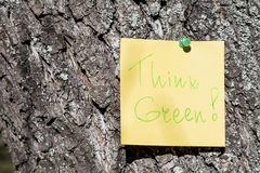 Yellow paper note with think green sign pinned on a tree Stock Image