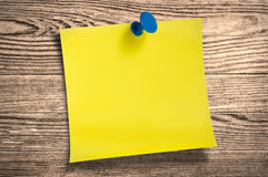 Yellow paper note  on wood, clipping path. Royalty Free Stock Photos