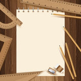 Yellow paper with pencil, ruler, eraser and sharpener on lath boards. Royalty Free Stock Photos