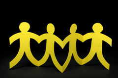 Yellow paper people on black background Stock Images